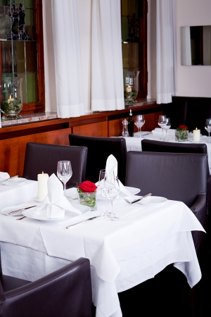 fine: tables in restaurant with white tablecloth and elegant dish and silverwear Stock Photo