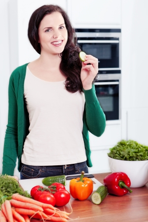 young woman cooking vegetarian food in kitchen photo