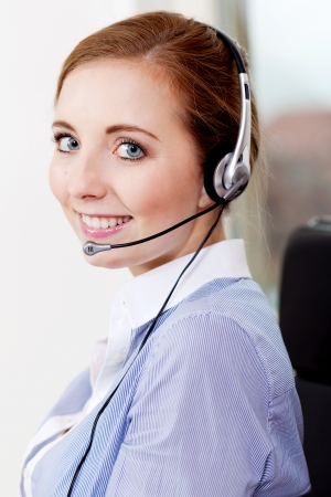 smiling young female callcenter agent with headset in office Stock Photo - 19187761