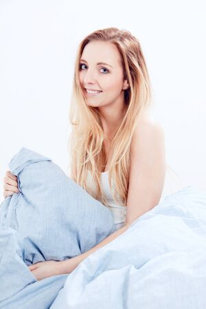 cute smiling blonde woman in the morning under blue blanket Stock Photo - 19459035