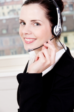 smiling young female callcenter agent with headset in office Stock Photo - 19447498