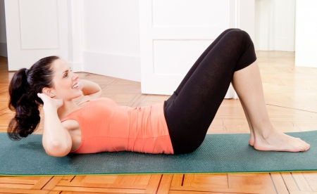 sit ups: attractive young woman doing sit ups at home sport workout Stock Photo
