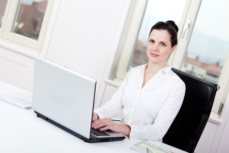 smiling young female callcenter agent with headset in office photo