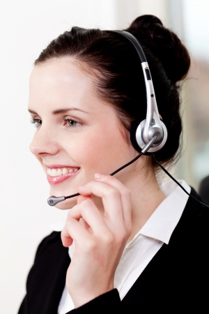 smiling young female callcenter agent with headset in office Stock Photo - 19446017