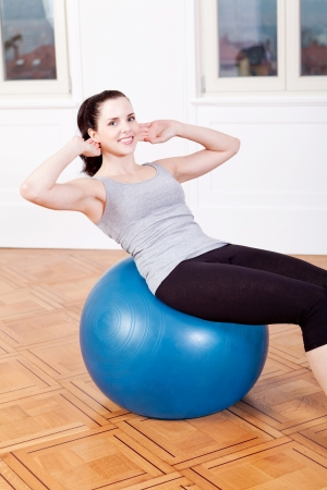 situps: attractive young woman doing sit ups at home sport workout Stock Photo