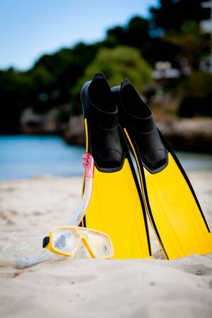 snorkelling: yellow fins and snorkelling mask on beach in summer holiday