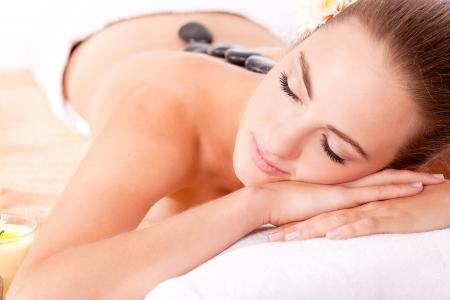 junge attraktive Frau Hot Stone Massage Wellness isoliert auf weiß
