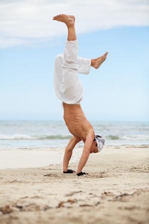 man is jumping sport karate martial arts fight kick jump beach summertime photo