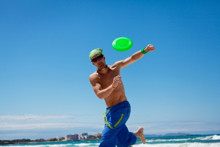 flying disc: attractive man playing frisby on beach in summer sport fitness jump