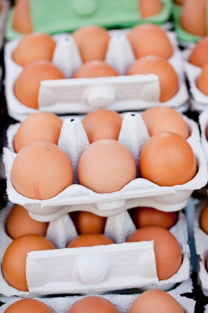 group of brown eggs in carton box closeup market outdoor photo