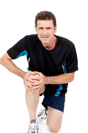 dolor de rodilla: atractivo hombre adulto en ropa deportiva dolor de rodilla dolor de una lesión aislada en blanco