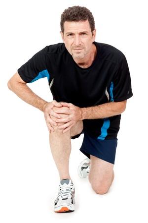 artrite: uomo adulto attraente in abiti sportivi dolore al ginocchio lesioni mal isolati su bianco