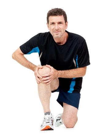 seniors suffering painful illness: adult attractive man in sportswear knee pain injury ache isolated on white Stock Photo