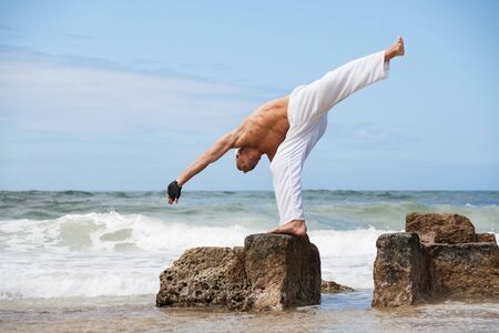 healthy man doing pilates yoga meditation on beach summer freedom photo