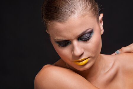 woman with extreme colorfull make up in blue and yellow on black background photo
