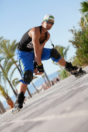 young man with inline skates in summer outdoor  photo