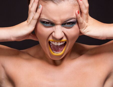 attractive young woman scream out loud with yellow lipstick on black background photo