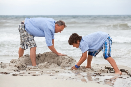 father and sons on the beach playing in the sand holiday family  Stock Photo