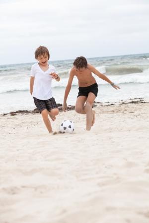 jugando futbol: Feliz padre de familia dos ni�os jugando al f�tbol en la playa del verano de la diversi�n del f�tbol