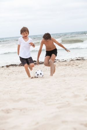 happy family father two kids playing football on beach summer fun soccer photo