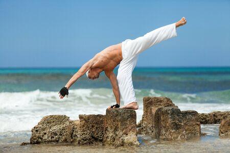 healthy man doing pilates yoga meditation on beach summer freedom photo