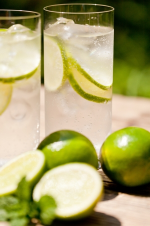 fresh cold refreshment drink mineral water soda with lime and mint on wooden table in summer Фото со стока