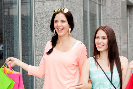 two attractive young girls women on shopping tour outdoor city summer  photo