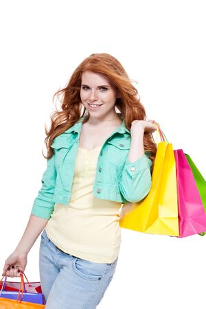 shoppingbags: smiling young redhead girl with colorful shoppingbags  isolated on white background Stock Photo
