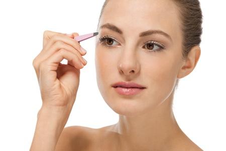 beautiful young woman and eyebrow tweezers isolated on white 写真素材