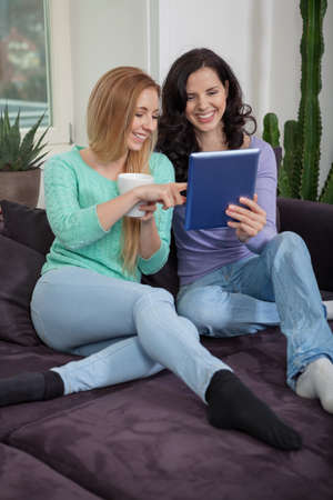 two young attractive girl with tablett pc on couch portrait lifestyle photo