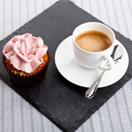 chocolate sprinkles: tasty sweet cupcake and hot aromatic espresso coffee on table Stock Photo