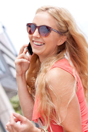 attractive young blonde woman talking on the phone outdoor in summer photo
