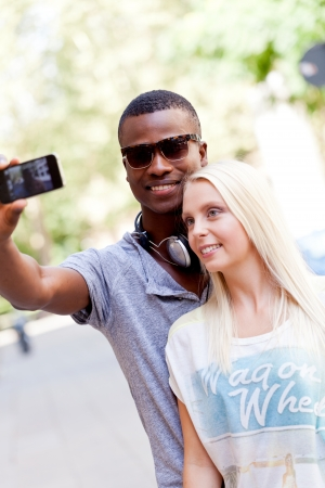 interracial couple: young smiling multiracial couple taking foto by smartphone outdoor in summer Stock Photo