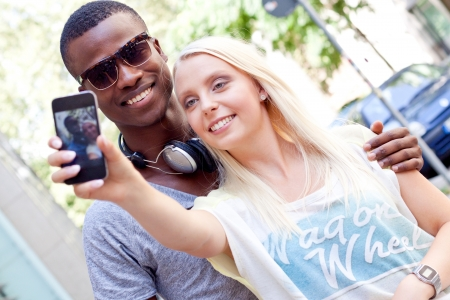 young smiling multiracial couple taking foto by smartphone outdoor in summer photo