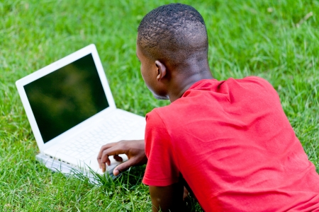 young smiling african student sitting in grass with notebook outdoor in summer man photo