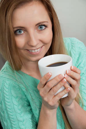 smiling young woman drinking coffee in the morning photo