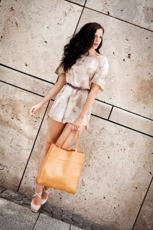 attractive young brunette woman in sexy dress and handbag outdoor in summer photo