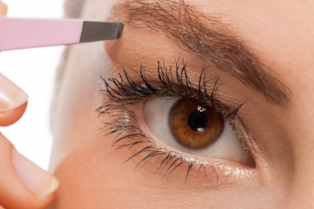 youtg beautiful woman eyebrow plucking tweezers eyes hair  closeup portrait