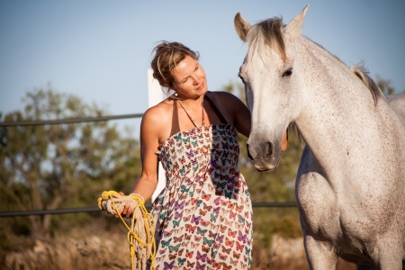 young woman walking away in sunset with horse summertime photo