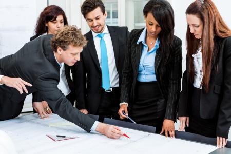 mensen uit het bedrijfsleven bespreken architectuur plannen schets in het kantoor Stockfoto