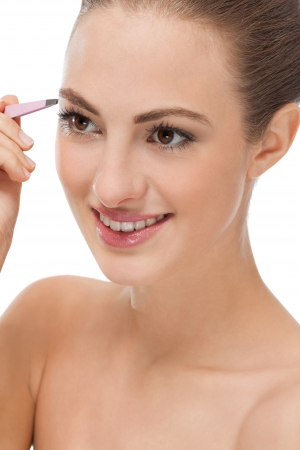 tweezing eyebrow: youtg beautiful woman eyebrow plucking tweezers eyes hair  closeup portrait