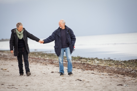 mature happy couple walking on beach in autumn lifestyle healthy