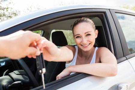 lachende jonge vrouw zitten in de auto nemen sleuteloverdracht huur aankoop Stockfoto