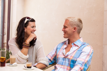 happy young couple sitting outside cafe restaurant drinking coffee  talking summer photo