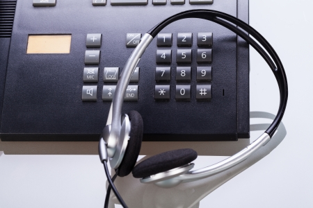 closing time: office desk with telephone and headset objects break work Stock Photo