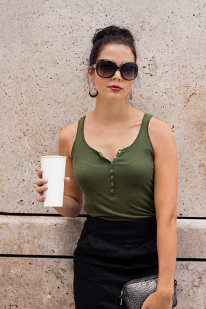 attractive young woman with coffee to go and sunglasses outdoor in summer photo