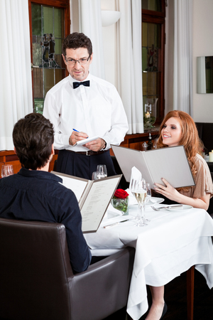 man and woman for dinner in restaurant waiter serving mineral water Stock Photo - 23810705