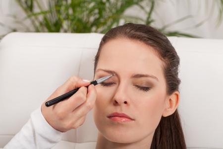 aantrekkelijke jonge vrouw make-up wenkbrauw poeder schaduw aanbrengen closeup schoonheid