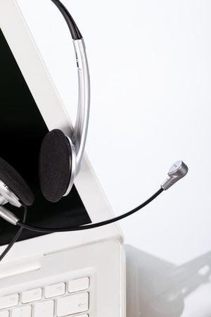 handsfree telephones: headset keyboard notebook laptop in office on table desk closeup objects Stock Photo