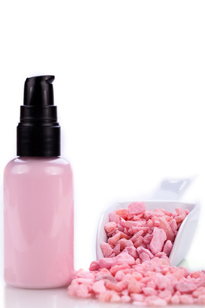 pink body lotion in dispenser and aroma salt isolated wellness spa cosmetic